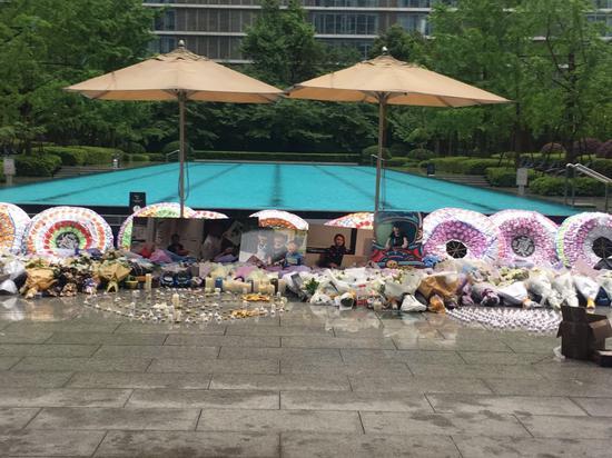 火灾后,小区业主自发组织悼唁活动,草坪上逝者照片前摆满了花圈、花束、蜡烛。新京报记者王婧祎摄