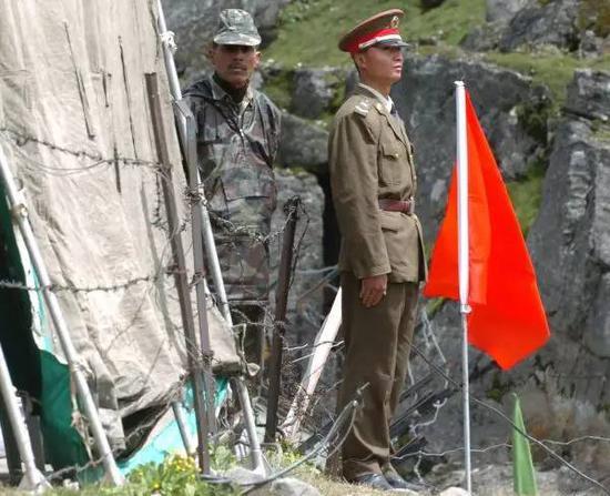 ▲资料图片: 2006年7月5日,在中印疆域乃堆拉山口,一名中国边防武士(右)与一名印度边防武士隔着界限的铁丝网值勤。