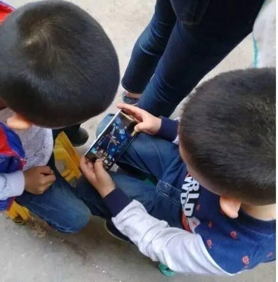 ▲小学生聚在一起玩手机游戏。图片来自网络
