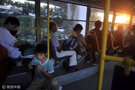 ▲广州市一辆公交车上,一位小学生坐在车内地板上玩着手机游戏。图/视觉中国