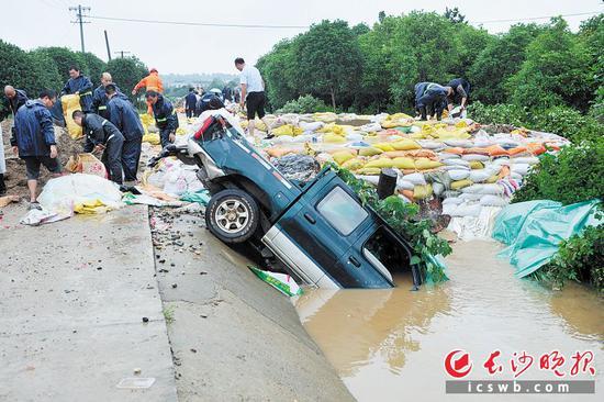 昨日上午,因为排洪渠呈现管涌,刘兵紧迫将自家皮卡车推入水中拦阻水势,并在前方用砂石袋垒出常设围堰,堵住管涌。长沙晚报记者 王志伟 摄