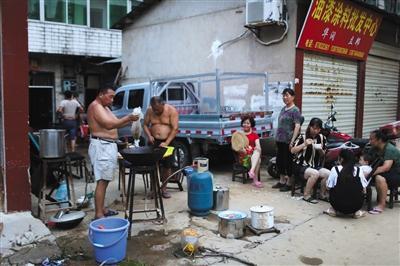 7月2日,宁乡群英路,因家中被水浸泡,以及停水停电,几家人在路边架锅做晚饭。
