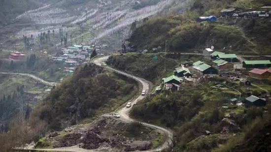 汽车在中印边境乃堆拉山口的盘山公路上行驶。