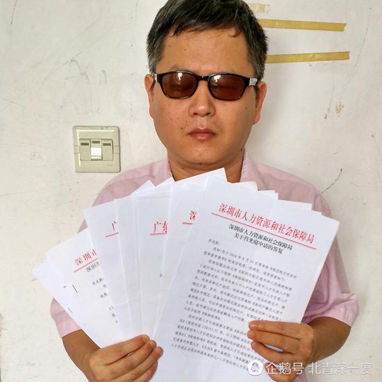 """盲人肖光庭拿着各部门关于""""积分入户""""政策的回复"""