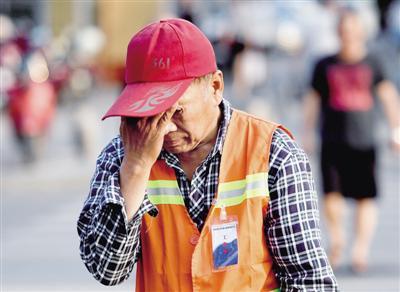 昨日,金水区环卫工刘师傅在烈日下打扫卫生,不时用手擦一把脸上的汗水。