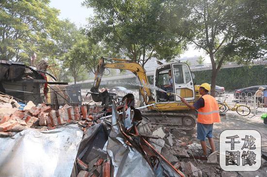 7月11日上午,北京东城龙潭街道组织城管、公安、工商、食药、街巷长等多方力量,对光明桥西北角4处违建进行了集中拆除。图为拆除现场。千龙网记者陈健男摄