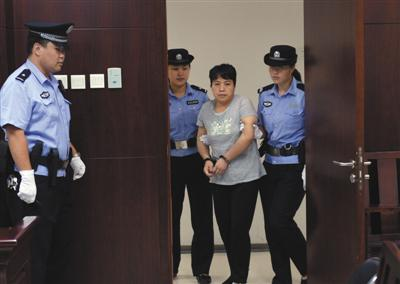 """昨日,胡某被带进法庭。这名扇警察耳光的传销公司库房女主管因""""劫夺被押解人员罪""""获刑3年半。新京报记者王贵彬摄"""
