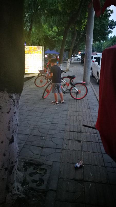 少年清理共享单车上的牛皮癣广告。