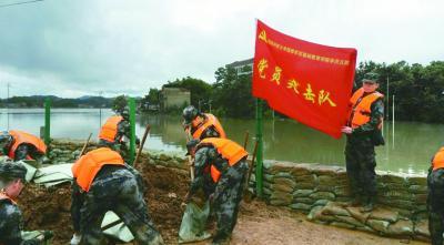 """抗洪现场,""""党员突击队""""的旗帜鲜红醒目。安子阳摄/光明图片"""