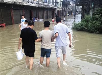2016年9月,浙江苍南县雨季,警方趟着城中积水将犯罪嫌疑人杨琛送进看守所。警方供图