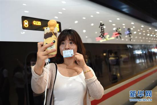 """6月26日,在北京南站,一位乘坐""""复兴号""""G123次列车的乘客在车外与列车合影。新华社记者鞠焕宗摄"""