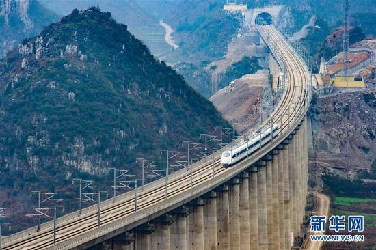 由昆明开往贵阳的G4136次列车经过贵州省安顺市境内的水桶木寨特大桥(2016年12月28日摄)。新华社记者 刘续 摄