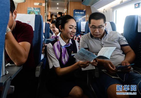 在上海虹桥站开往郑州东站的G1802次列车上,乘务员夏梦雅给乘客发放宣传资料,讲解注意事项(2016年9月10日摄)。新华社记者季春鹏摄