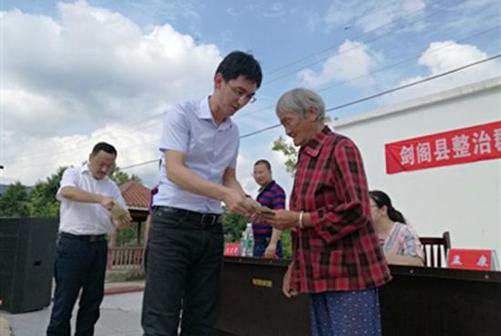 村民从剑阁县纪委书记母雪龙手中领到退返的2600余元违纪款项。成都商报图