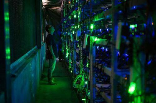 四川省西部山区的一个比特币矿场的经理正在检查设备。(美国《华盛顿邮报》网站)