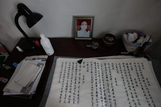 ▲2017年7月17日,赵菁家中的写字台上,摆放着母亲的遗照和书法习作。这一年来,她经常通过练习书法的方式平复自己的情绪,同时消磨在家修养的时间。