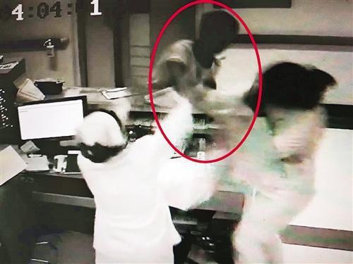 陈某(画圈处)拿起护士站台上的意见箱砸向女护士小陈(视频截图,警方提供)