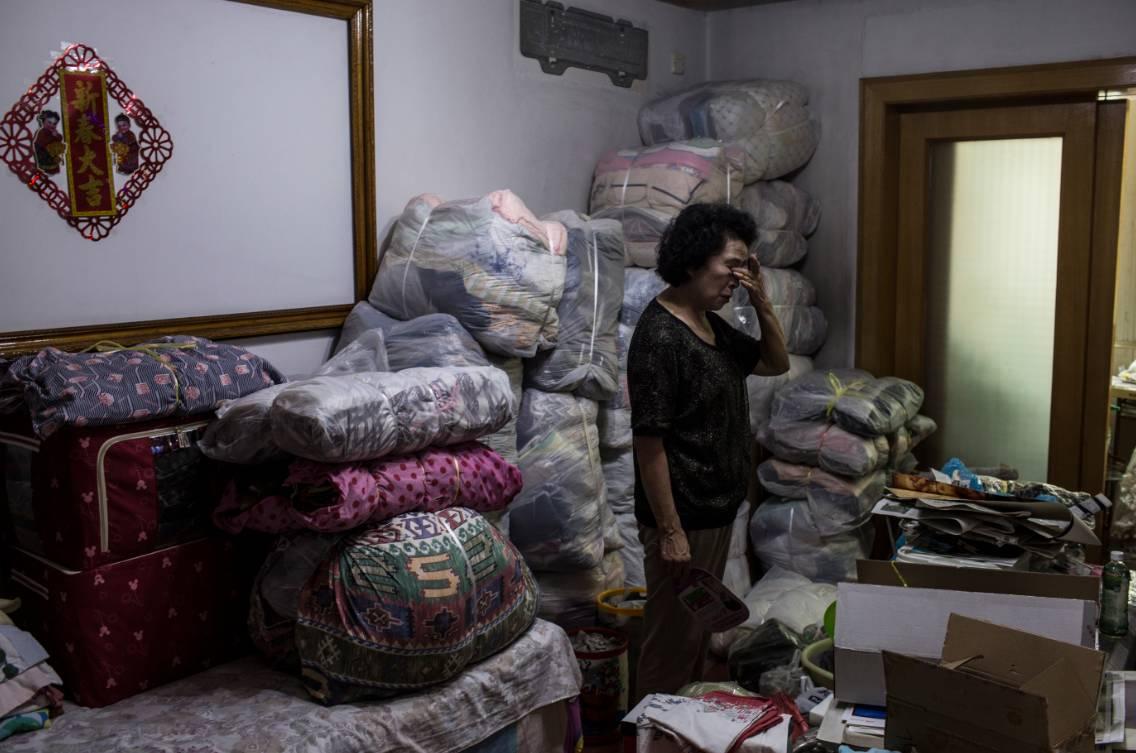 受骗老人吴老太在家中收拾行李,房子被二次过户后,新房主要求她在三天之内搬走。