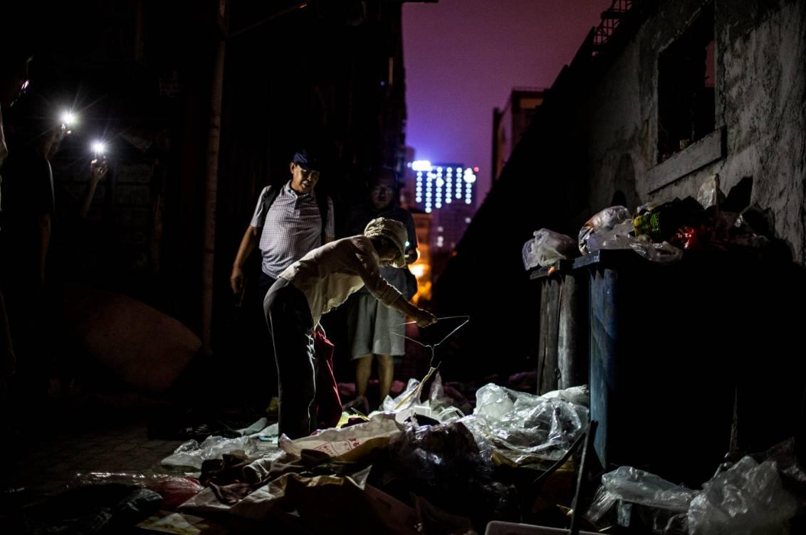 80岁的张秀兰白天接到邻居电话,他们的行李又被扔出来了,夜里老人在楼下整理他们的行李。