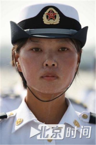 烈日灼人,但女兵纹丝不动,脸上透着坚毅。资料图