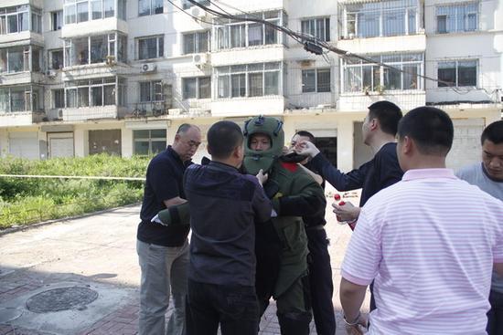 成功排爆后,同事们正在帮朱建民脱下防爆服,防爆服重达70斤。