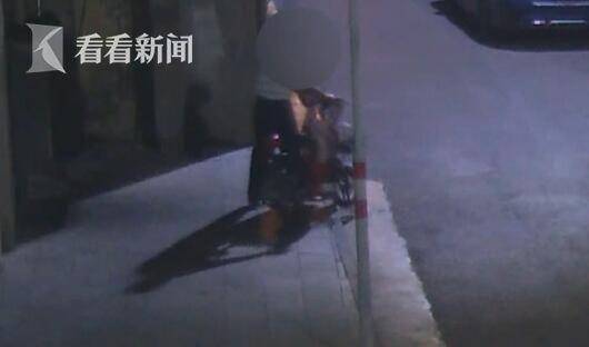 监控画面显示,一名男子走到一辆电动车边,脚踩一下后轮,确认这辆车没有上锁之后,将这辆车推走。