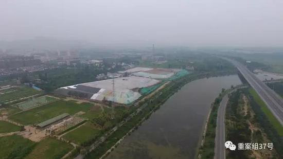 ▲露天垃圾填埋场一侧距离居民区的距离在300米左右。 新京报记者王飞 摄