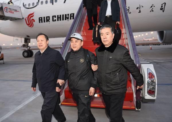 王国强(中)回国投案自首,到达首都机场