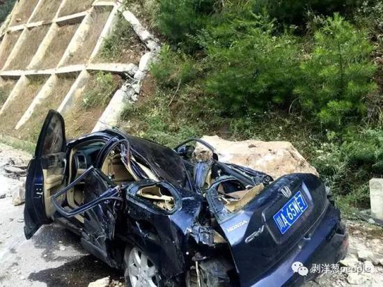 一辆轿车被山上滚落巨石砸扁。