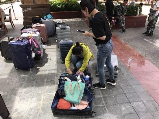 ▲工作人员正向游客视频确认箱子里物品是否齐全。工作人员说,只有跟失主视频时,他们才能开箱。