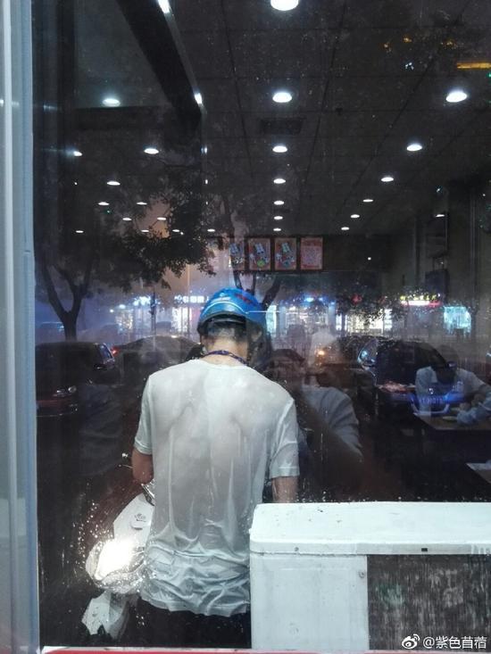 从照片中可以看到,这位外卖小哥的体恤已经淋湿透了。