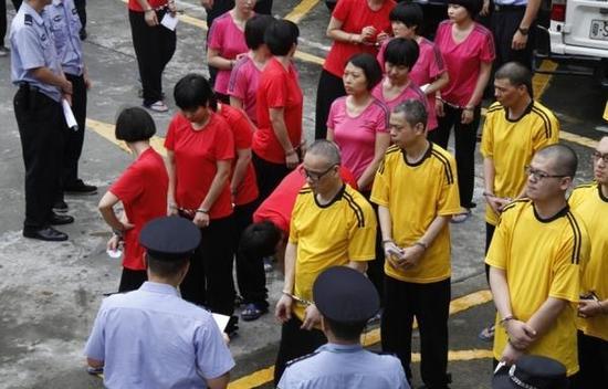 2015年5月27日,包括梁耀辉(穿黄衣者左一)在内的47人出庭受审。 东方IC 图