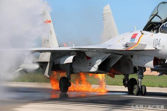 袁伟驾驶的歼-15舰载战役机着陆后,受损的左动员机燃起了年夜火。王俊柯摄