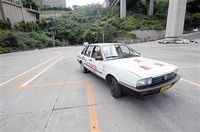 18日,江北区一驾校教练在指导学员举行侧方位停车的训练。本报记者 胡杰 摄