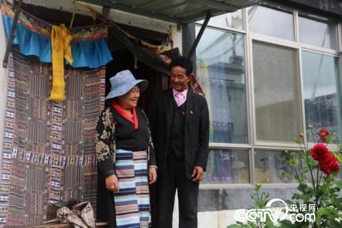 村民扎西多吉与妻子在新房子门口开心地交谈