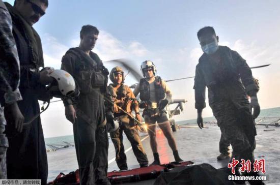 资料图:当地时间8月23日,在马来西亚附近海域,马来西亚海军和美国海军寻获一具失踪船员遗体。图为美国海军将遇难者遗体运上直升机。