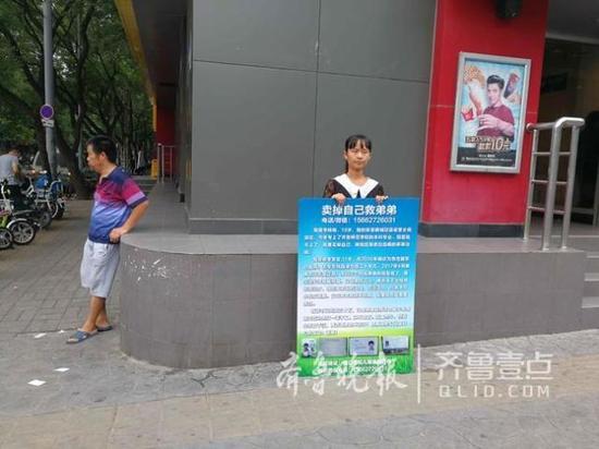 """在街头举牌""""卖身""""的李晓晓,四周是她父亲。"""
