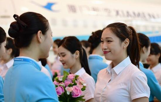 8月16日,第一批台湾籍空中乘务员(右)蒙受厦航空中乘务员奉上的欢