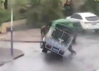 周荣在台风中扶车,被压身亡。 视频截图