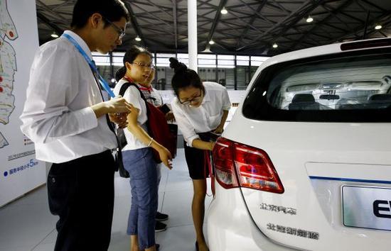 资料图片: 2017全球新能源汽车大会未来汽车展在沪举行。8月3日,工作人员向参观者介绍一款电动汽车充电指标。  新华社记者 方喆 摄