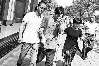缪新华(左一)12日走出法院,重获自由图片来源:北京青年报