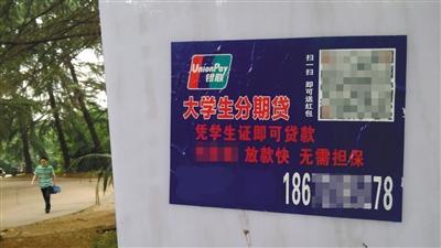 """某高校校园内张贴的大学生分期贷广告,宣称""""凭学生证即可贷款,放款快,无需担保。""""图/视觉中国"""
