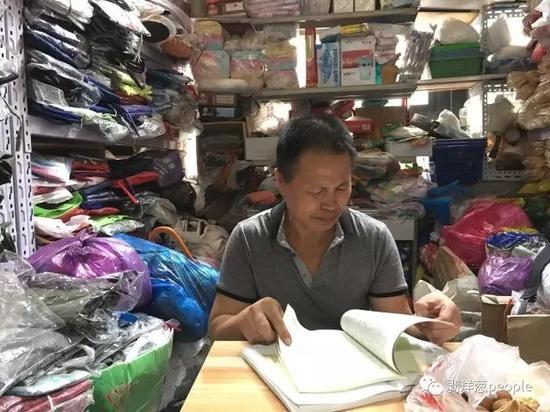 张焕财在他的劳保用品店看书。