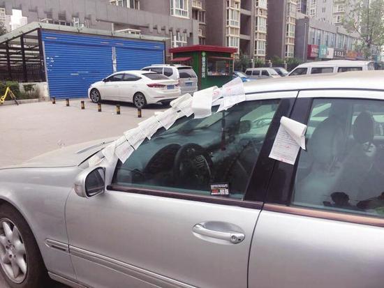 西安北郊泰和居小区门口,一辆停放在路边的奔驰车上,竟被贴了十余张罚单。这到底是怎么回事?