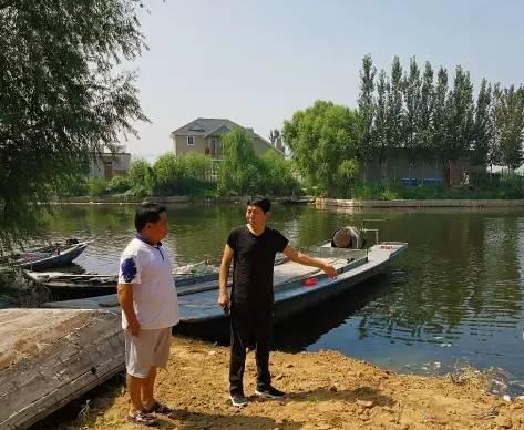 安新县乡村干部查看东田庄村内码头垃圾清理情况。