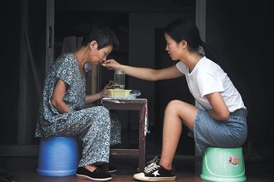 9月9日,江西南昌,赵金凤在出租房里陪母亲吃午饭。图片来源:新京报