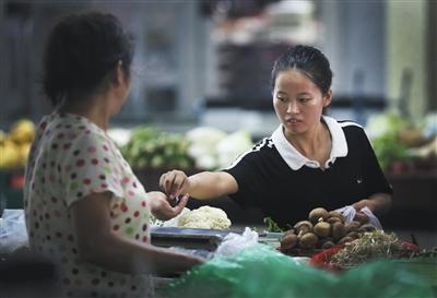 9月8日下午5时,赵金凤在菜市场买蔬菜。母亲平时只能吃素食。图片来源:新京报