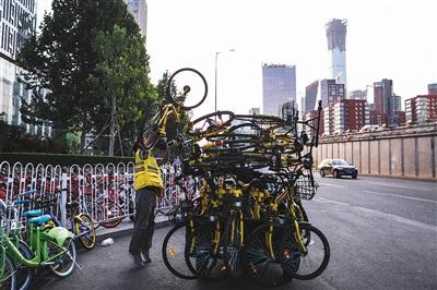 9月15日,大望桥四周,一位调理职员正用三轮车转运积压的共享单车