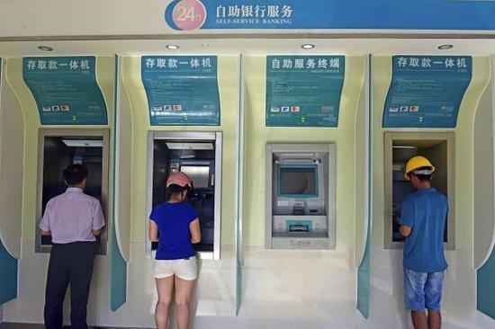7月31日,储户在海南琼海的一处银行自动柜员机前管理营业。
