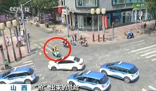 紧接着的这位送餐员,不仅闯灯过马路,而且被卡在两条车流中间,进退两难。